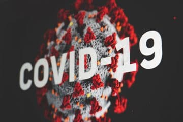 Covid-19 word with microscropic view of bacteria background