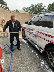 EMS Chief David Torsell III washing one of the new EMS SUVs.