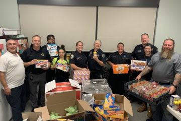 Escambia and New Orleans EMS personnel posing with a variety of snacks and bread