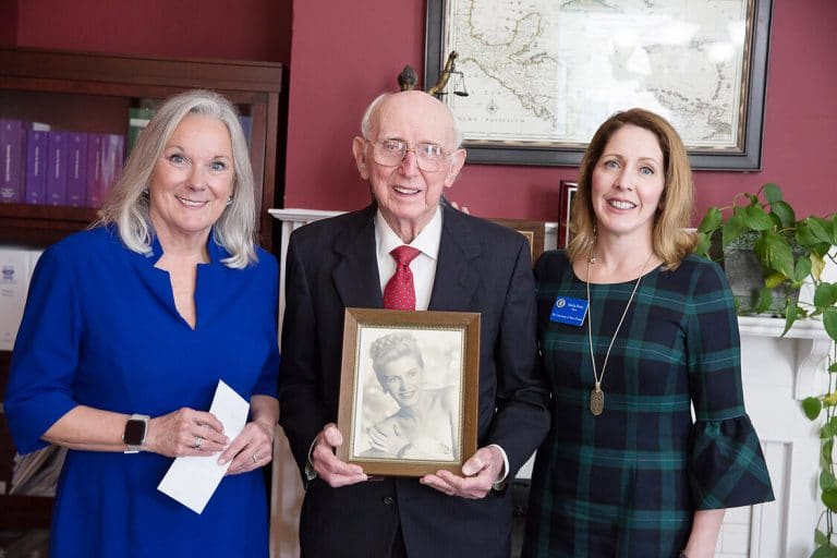 UWF President Martha D. Saunders, Dr. Herman Rolfs holding a portrait of Valerie Rolfs and Dr. Sheila Dunn